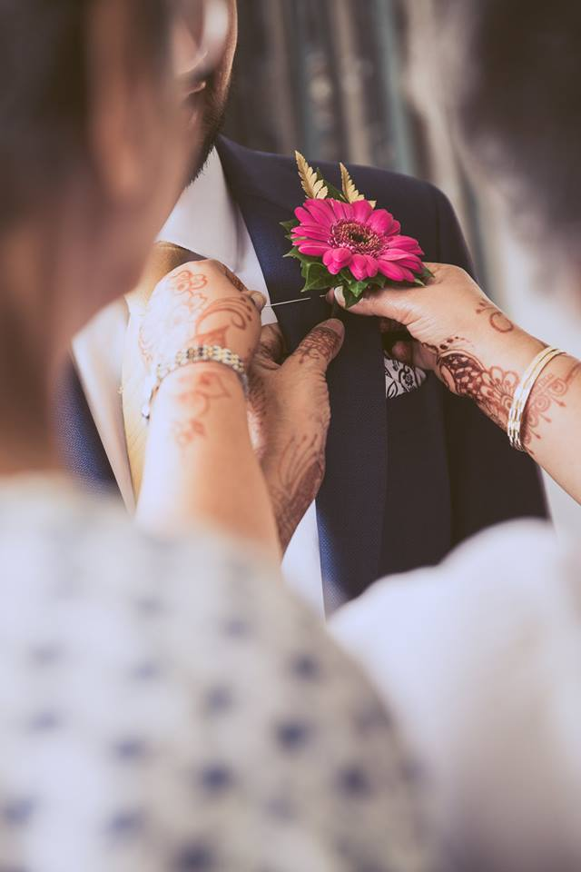Abstract+photo+of+someone+pinning+a+flower+to+the+grooms+suit+jacket