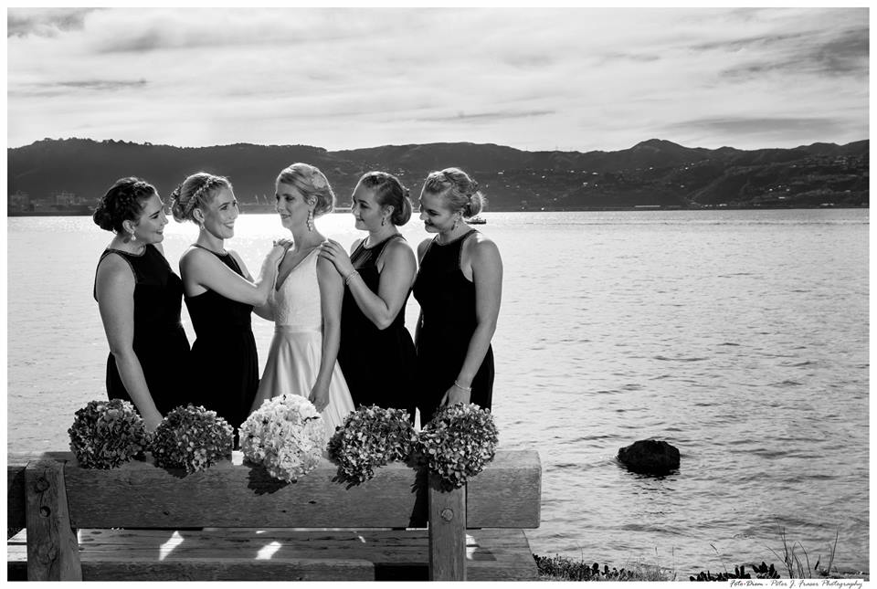 Bride+and+bridesmaids+standing+together+long+Wellington+waterfront