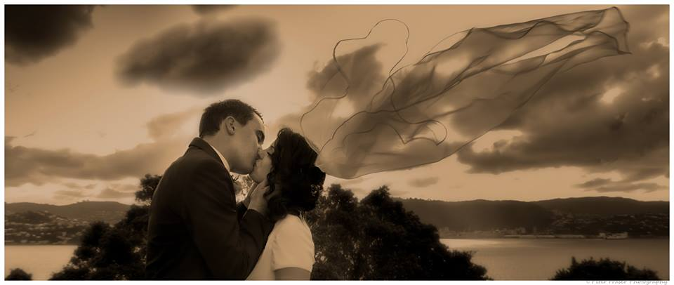 Bride+and+groom+kissing+with+dramatic+landscape+in+the+background