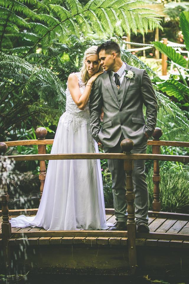 Bride+and+groom+standing+on+wooden+arch+bridge+with+greenery+in+the+background