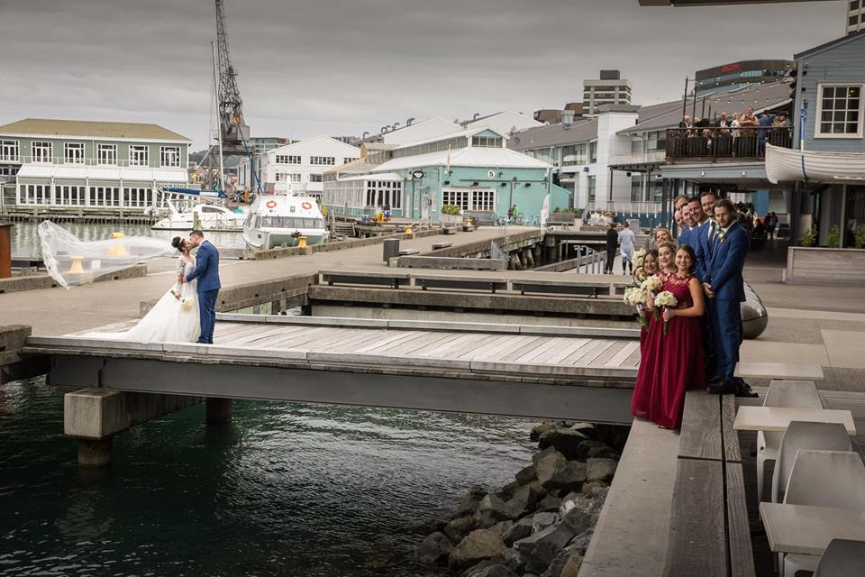 Bride+and+groom+standing+on+wooden+wharf+with+bridal+party+at+the+end+of+the+dock (1)