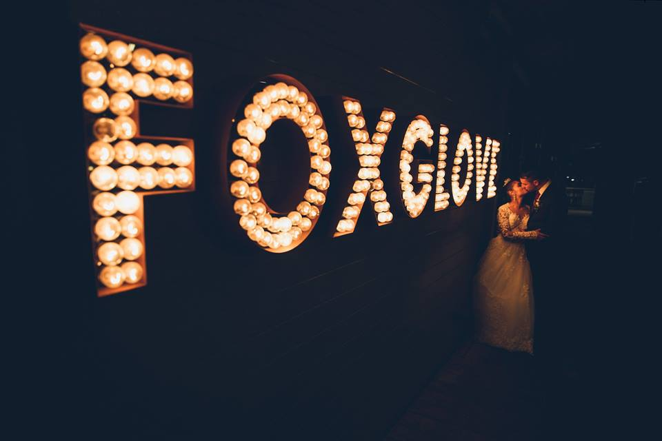 Bride+and+groom+standing+together+at+the+end+of+a+lit+up+sign