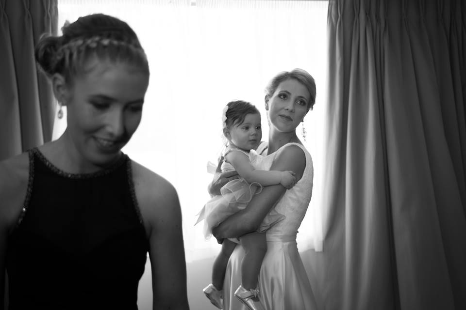 Bride+holding+flower+girl+with+bridesmaid+in+foreground