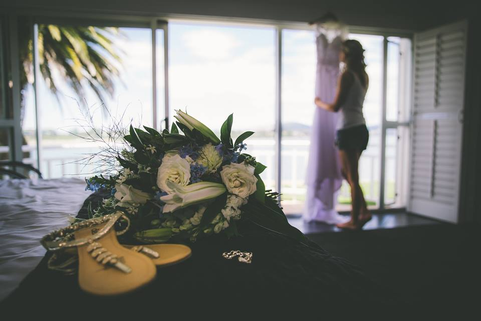 Brides+flowers+and+shoes+in+foreground+with+bride+in+background+standing+next+to+dress