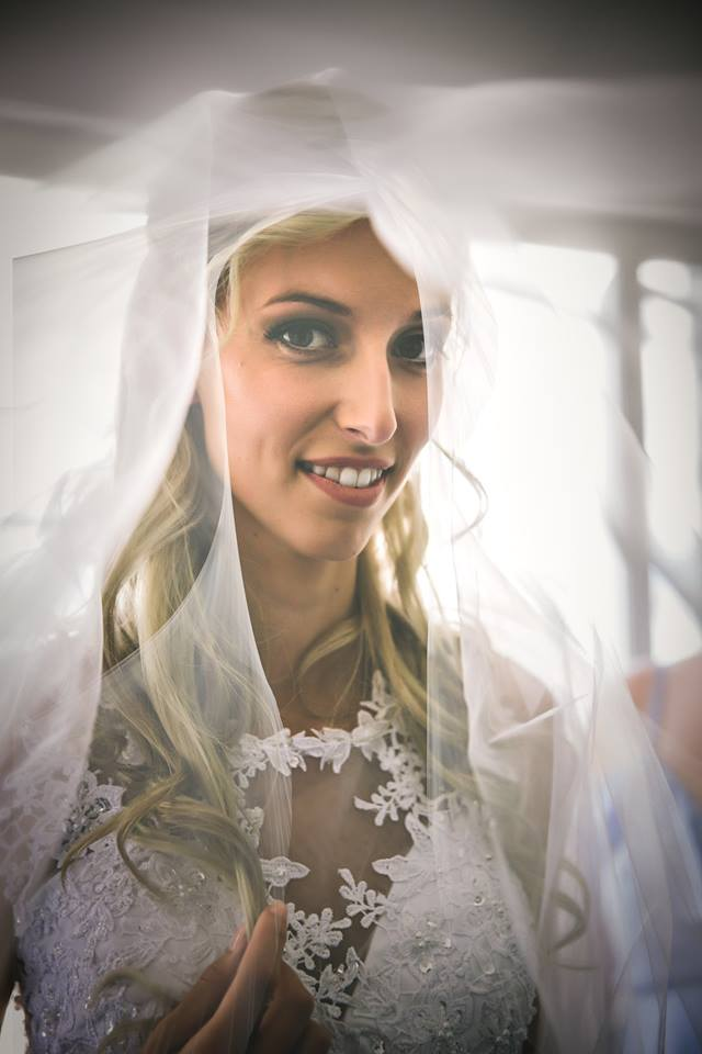 Chest+up+shot+of+bride+in+wedding+dress+looking+through+her+vale