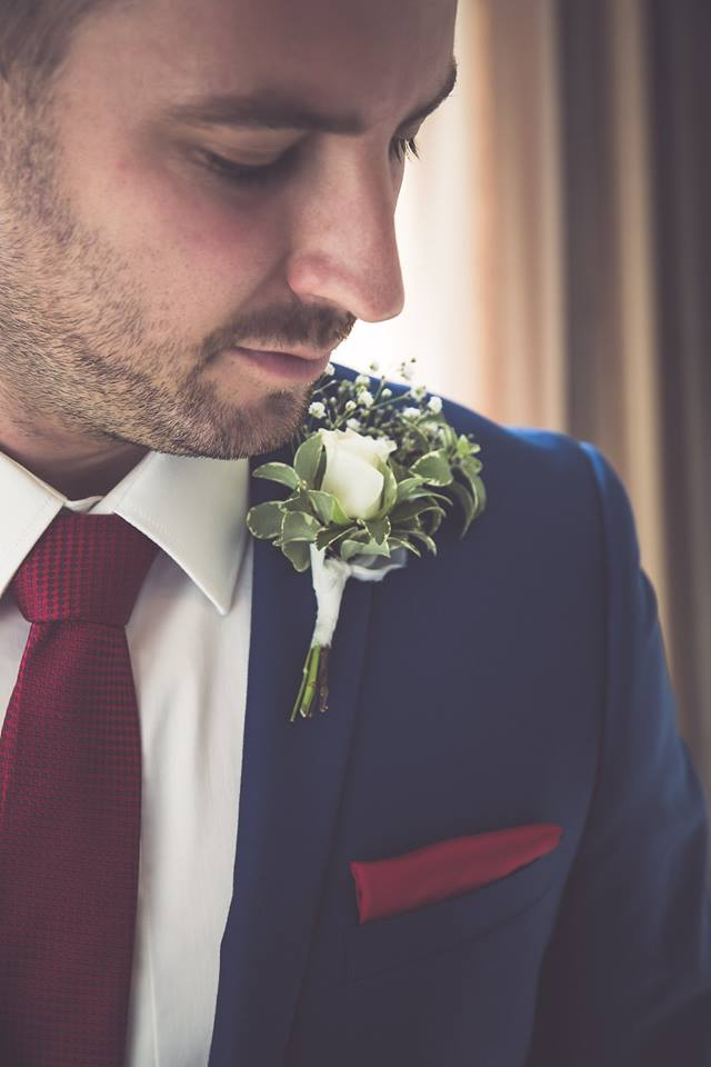Close+up+of+groom+looking+at+the+white+flower+on+his+lapel