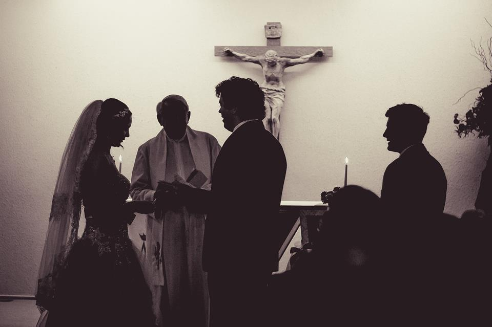 Dark+silhouettes+of+bride+and+groom+standing+together+at+the+alter+with+the+priest