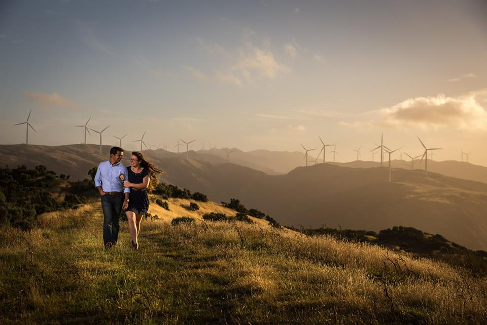 Engaged+couple+walking+along+hilltop+in+Welligton+with+wind+turbines+in+the+background (1)