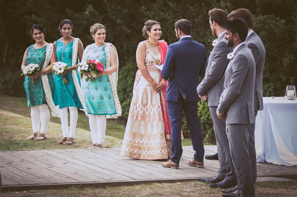 Full+length+photo+of+bride+and+groom+standing+together+holding+hands+with+bridesmaids+and+groomsmen+standing+beside+them