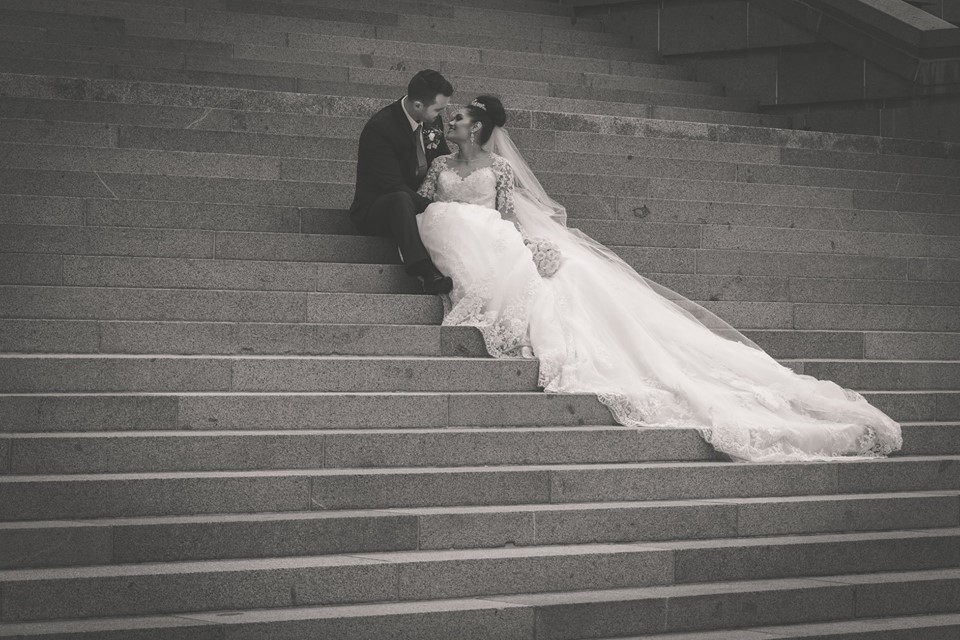 Groom+and+bride+sitting+on+steps+with+brides+train+trailing+down (1)