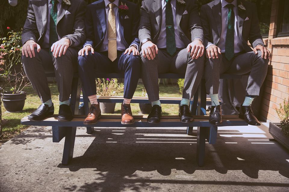 Groom+and+groomsmen+sitting+on+picnic+table+with+hands+on+their+knees