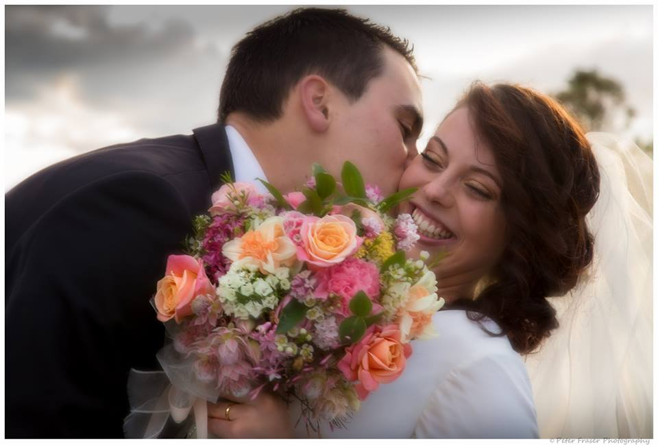 Groom+kissing+his+bride+on+the+cheek+while+she+holds+her+bouquet