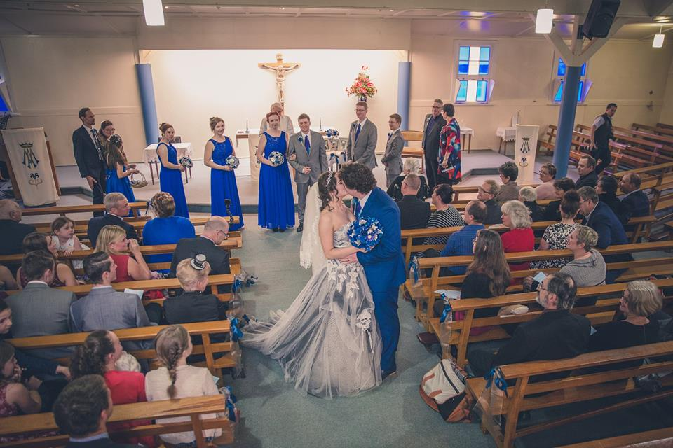 High+angle+shot+of+bride+and+groom+kissing+midway+down+the+aisle