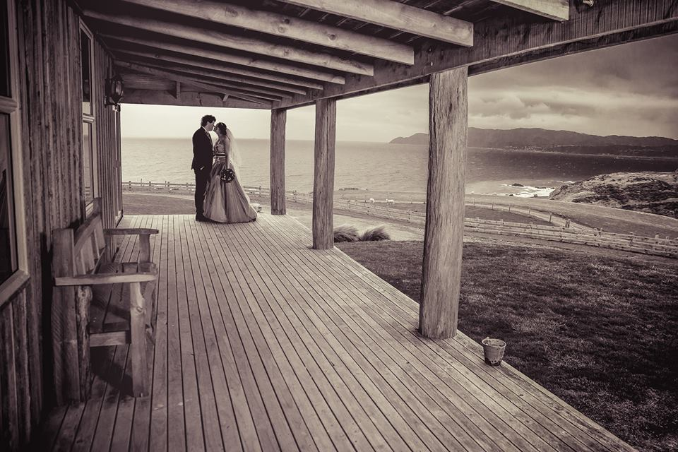 Mid+distance+photo+of+bride+and+groom+standing+together+under+wooder+porch