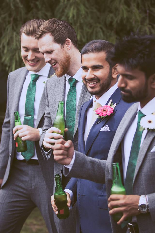 Mid+distance+shot+of+groom+and+groomsmen+standing+togther+drinking+a+beer