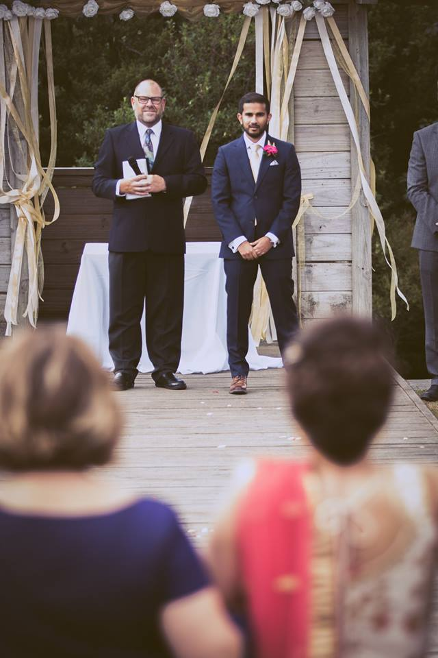 Mid+distance+shot+of+the+groom+waiting+at+the+alter+for+his+bride