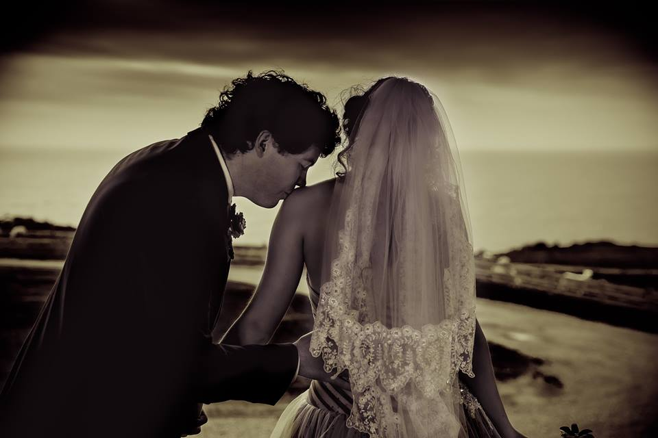 Photo+from+behind+of+the+groom+kissing+his+bride+on+the+shoulder
