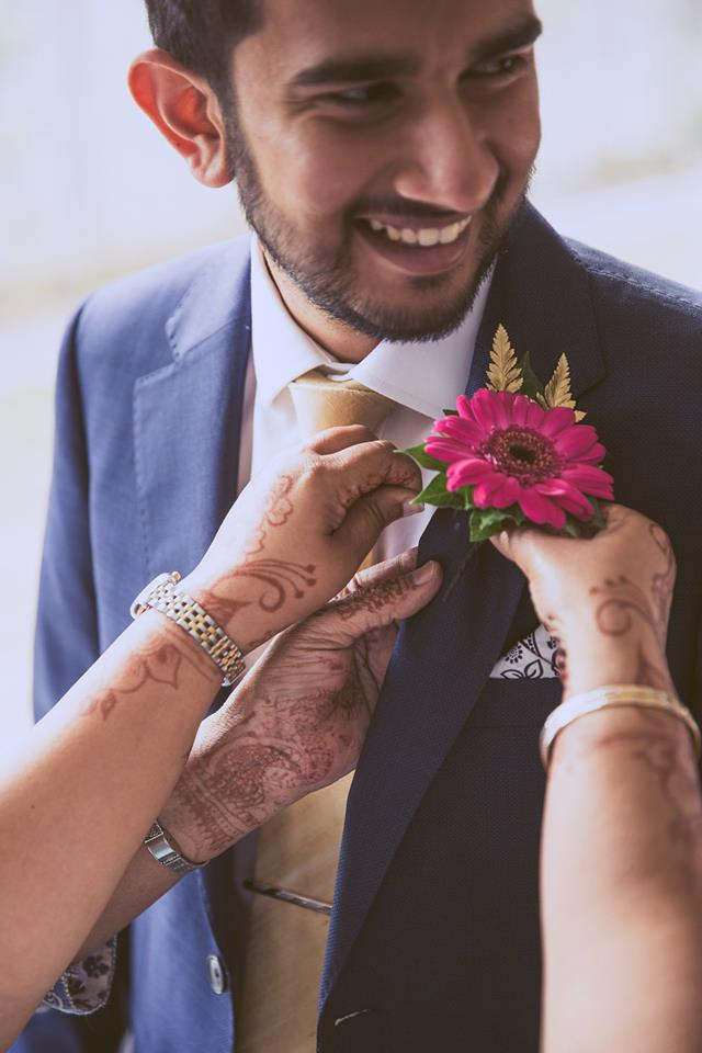 Pinning+a+flower+to+the+grooms+suit+jacket
