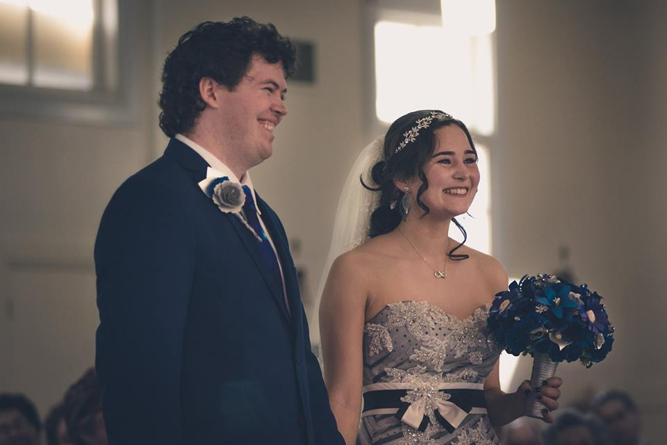 Slight+low+angled+photo+of+bride+and+groom+holding+hands+during+their+wedding+ceremony