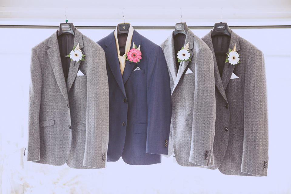Suit+jackets+of+the+grooms+and+groomsmen+hanging+on+a+rack