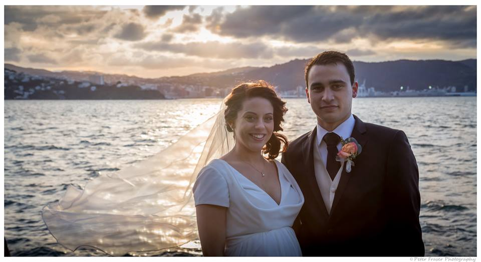 Waist+up+photo+of+the+bride+and+groom+standing+together+in+front+of+the+ocean