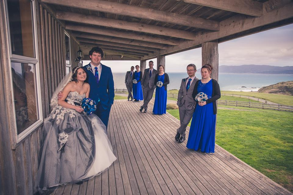 Wedding+party+standing+in+pairs+on+a+wooden+porch+with+sea+and+sky+in+background