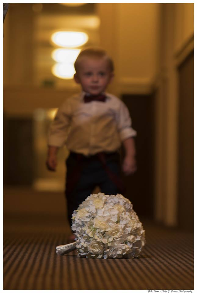 Young+page+boy+approaching+brides+bouquet