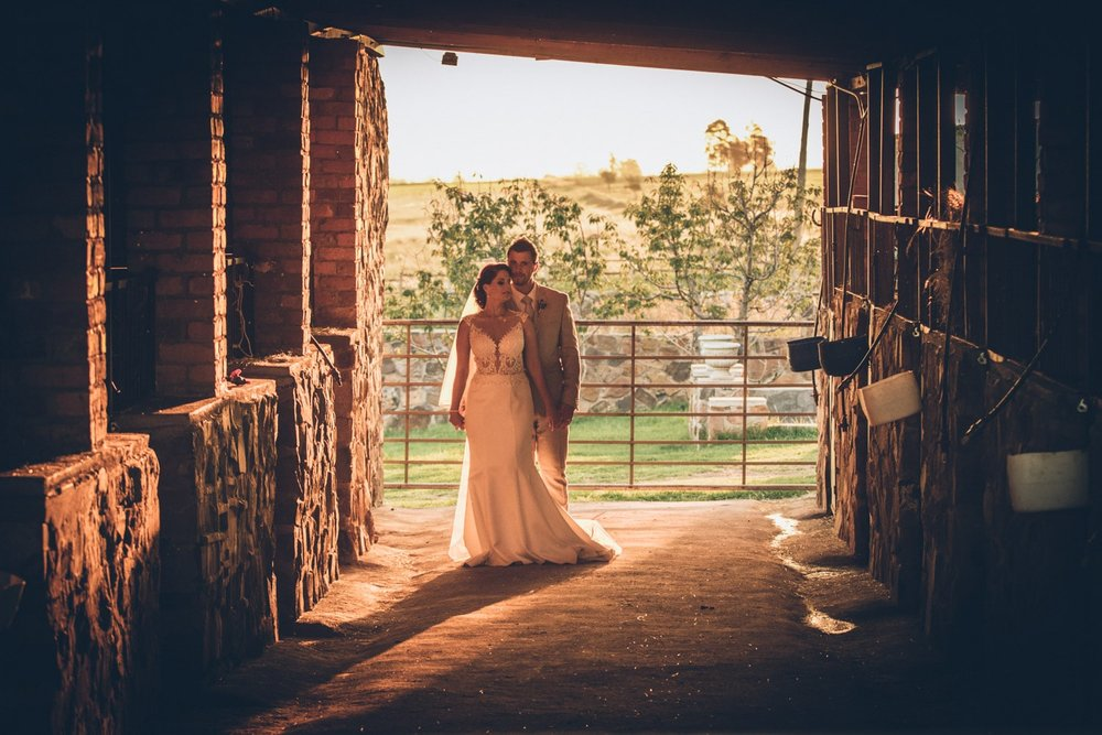 Bride+and+groom+standing+in+stables