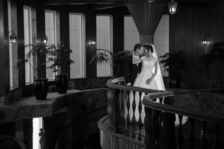 Bride+and+groom+standing+on+a+balustrade+in+an+ornate+and+elegant+hall