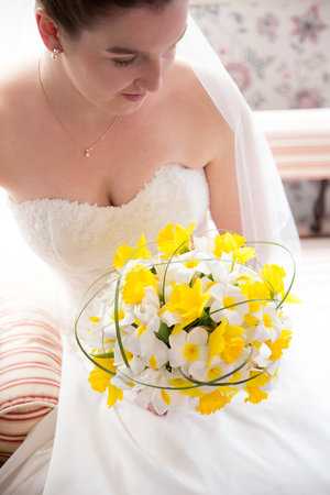 Bright+high+angle+photo+of+bride+sittin+on+chaise+holding+yellow+and+white+flowers