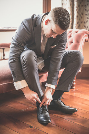 Groom+tying+his+shoes+on+hiw+wedding+day